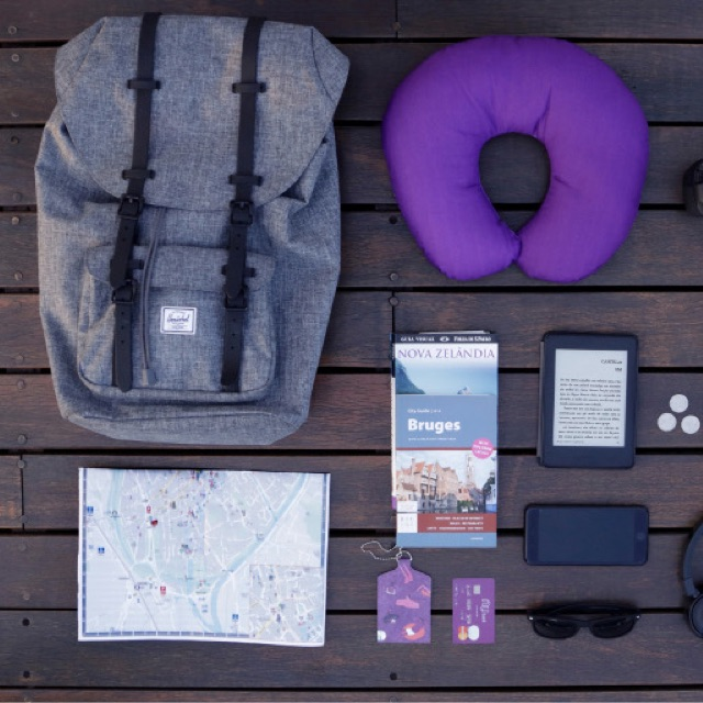 Como planejar uma viagem: vista de cima de uma mochila cinza, um mapa de cidade, um guia de Bruges, um  cartão Nubank e um travesseiro de viagem roxo