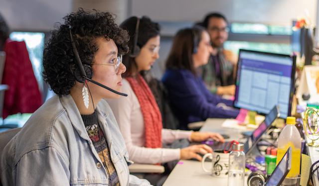 Carreiras por trás da conta do Nubank: foto de quatro pessoas com fones de ouvido com microfone trabalhando numa mesa compartilhada.