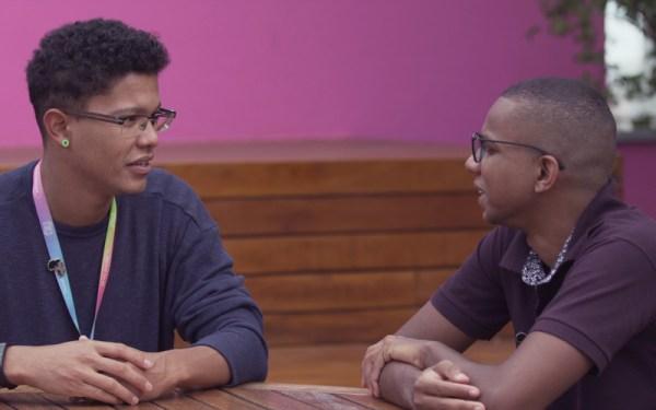 Ramon conversando com Nubanker. Ele está de blusa azul e de manga comprida e Ramon com uma blusa roxa de manga curta e óculos.