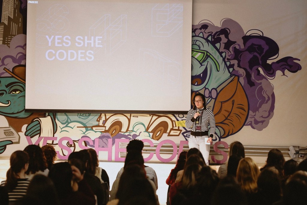 Imagem de uma mulher falando em um palco falando para várias mulheres na plateia.