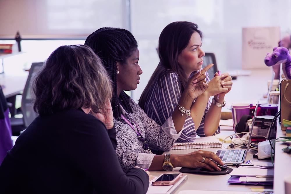 Três mulheres sentadas lado a lado  no escritório olhando para uma tela de computador. Uma delas aponta o dedo para frente.
