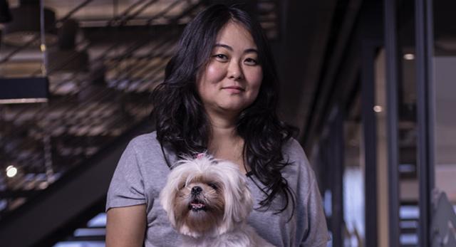Imagem de uma mulher sentada, olhando para a câmera. Ela veste uma camiseta cinza e segura um cachorro no colo