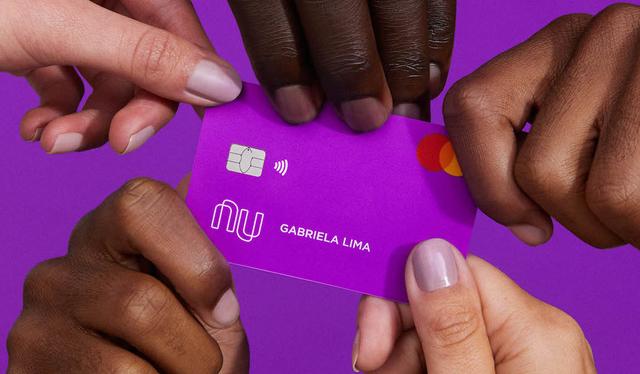 Débito Nubank: no fundo roxo, cinco mãos seguram o cartão Nubank
