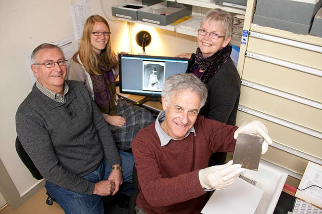 Errol Shaw holds the 50,000th glass plate to be digitised and relocated as part of the Nelson Provincial Museum's Glass Plate Negative Project. Pictured with Errol are fellow project team members (from left) Ian McGuire, Megan Wells and Anne McEwan. Image courtesy of Nelson Provincial Museum.