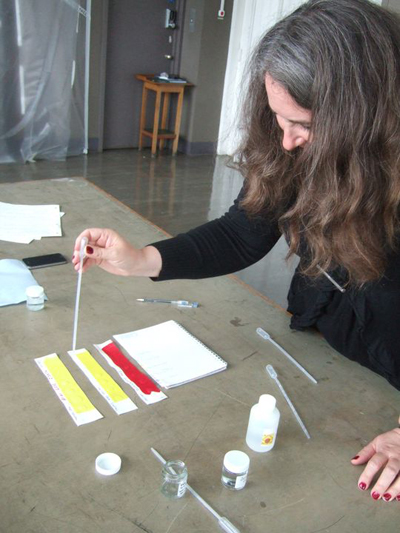 Annette King, Painting Conservator, Tate, assessing swelling caused by cleaning solutions. Image courtesy of Sarah Hillary, Auckland Art Gallery.