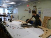 Ruth painting plywood decorations for the Foo Fest artist booths in AS220 Industries.