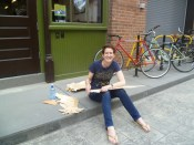 Ruth sanding plywood birds for Xander Marro's Foo Fest artist parade outside AS220 Industries.