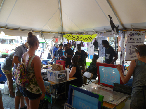 AS220 Youth programme's 'YouthBooth' with the AS220 Print Shop's demo table on the right. A staff member holds a silkscreen showing one of Foo Fest artist in residence Xander Marro's designs.