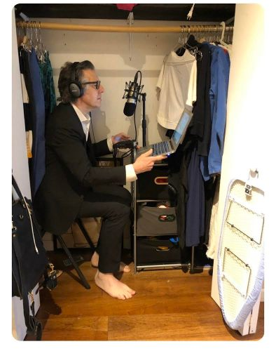 NPR host Ira Glass with his audio recording set up in a closet at his home.