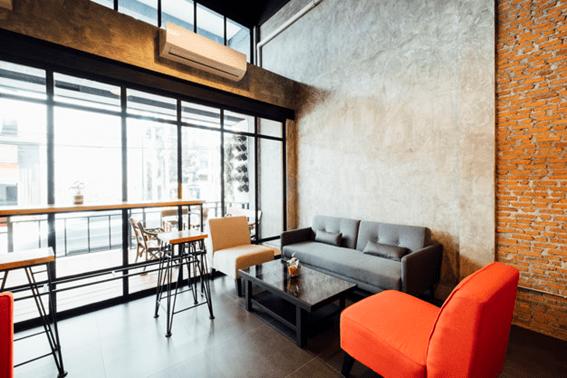sala de estar de uma empresa com sofás cinzentos e cor de laranja, mesa de centro, preta e ar condicionado fixo na parede