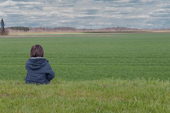 criança pequena sentada num vasto espaço verde no meio do nada a praticar mindfulness para crianças