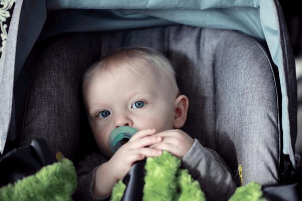 bebé loiro e de olhos azuis sentado numa cadeira auto para crianças pequenas no banco traseiro do carro
