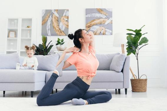 jovem mulher a praticar yoga na sala com a sua filha