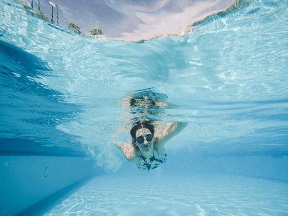 jovem mulher com óculos de natação a dar um mergulho numa piscina