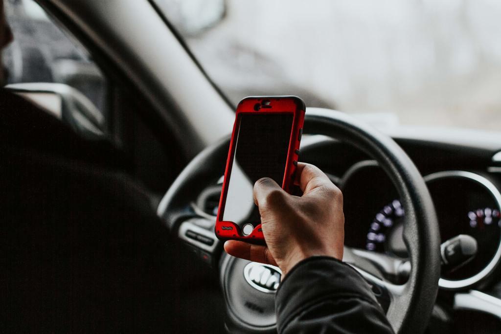 Pessoa a segurar smartphone sentada em frente ao volante do veículo