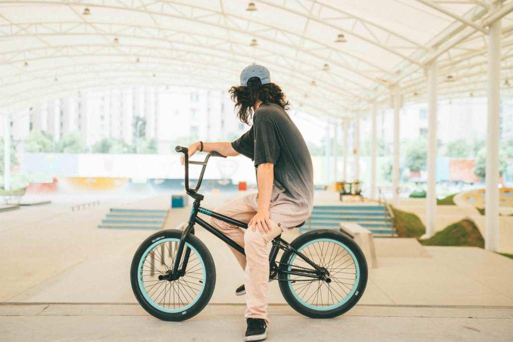 Jovem piloto bmx sentado na bicicleta