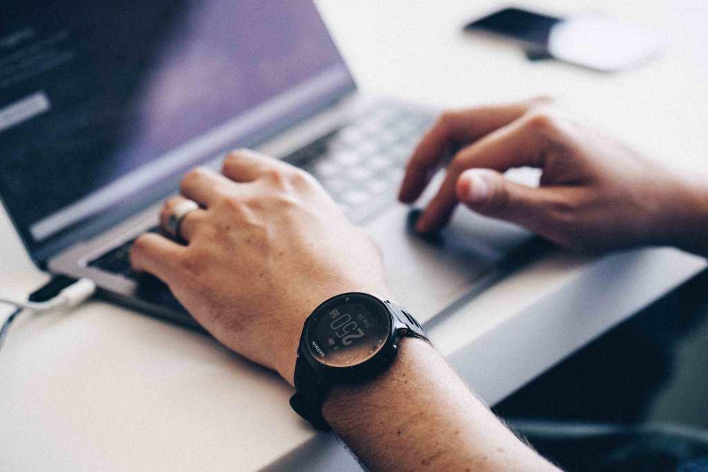 Homem com smartwatch a trabalhar no computador