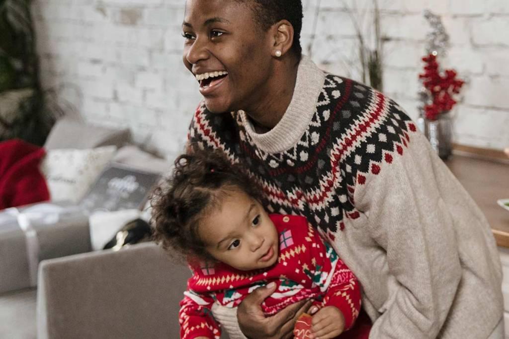 Mulher com camisola de natal a carregar bebê