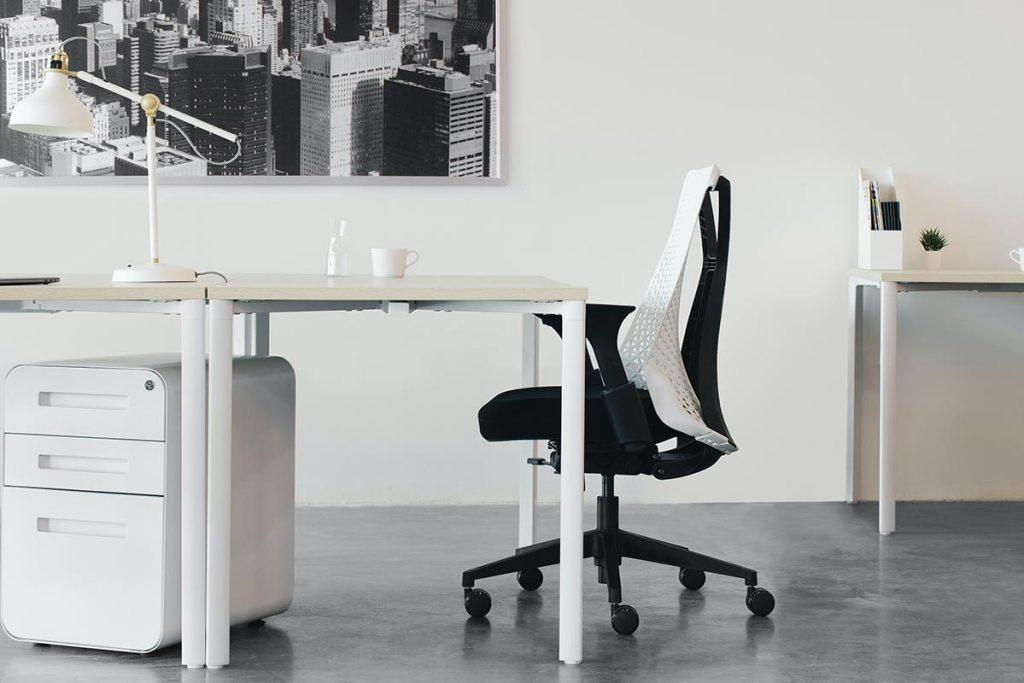 Cadeira de escritório preta ao lado da secretária