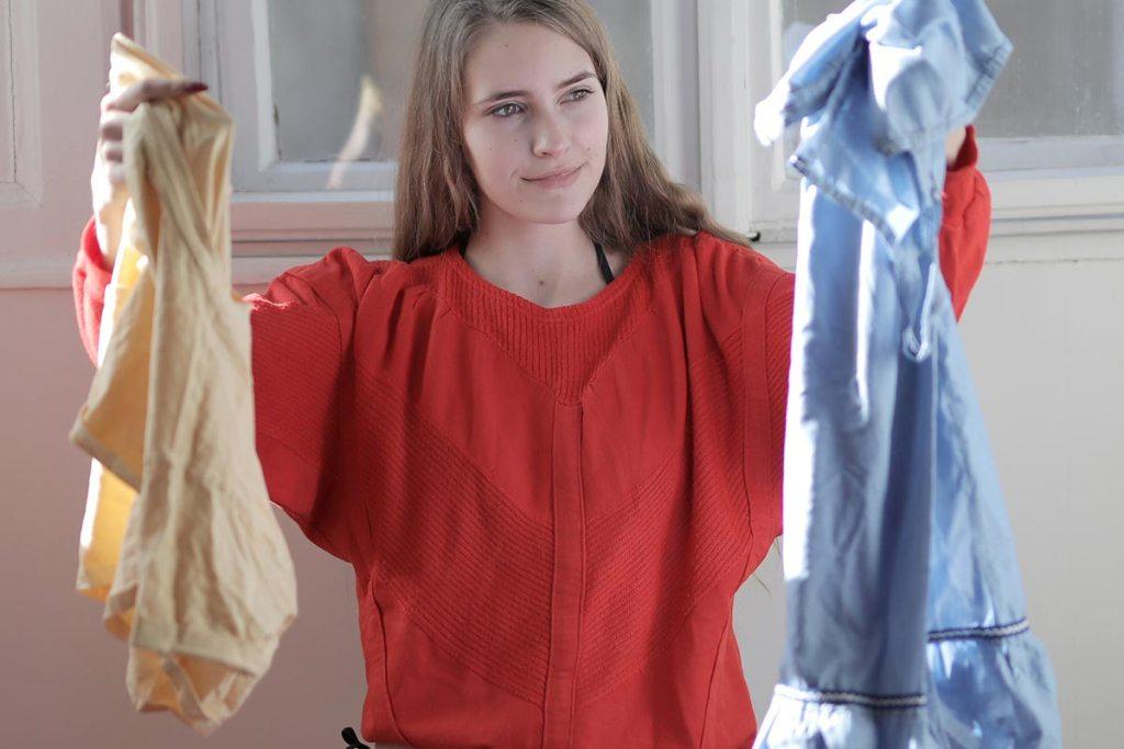 Mulher a escolher roupas para pôr na máquina