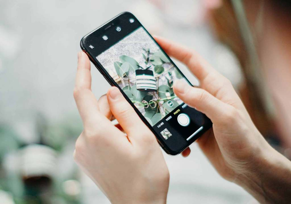 Mulher a tirar fotografia com smartphone recondicionado