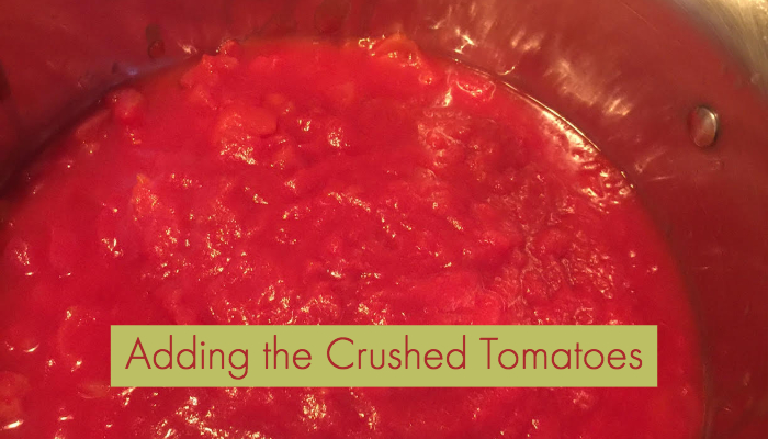 adding crushed tomatoes to chili
