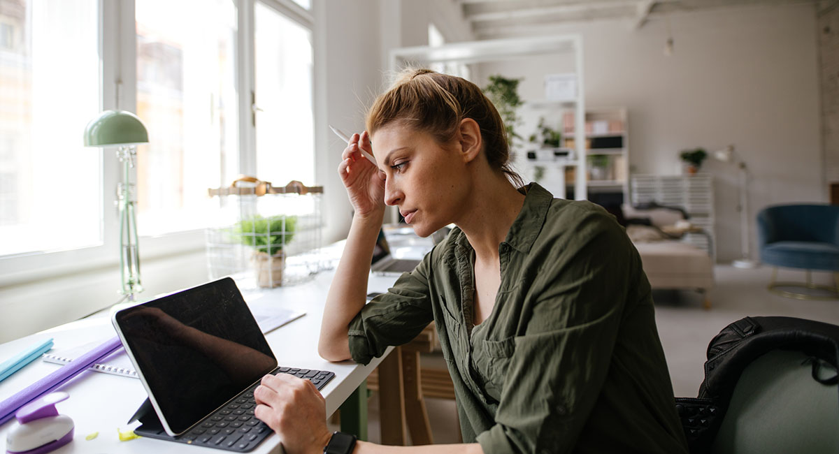 Woman sitting at computer, with hand on head