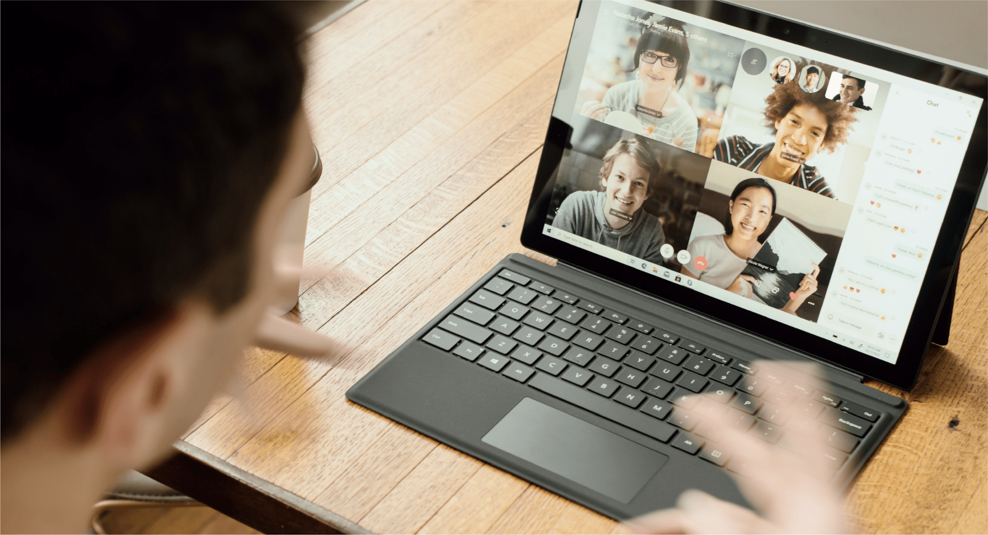 A man looks at a laptop with a video call where four team members are visible on screen