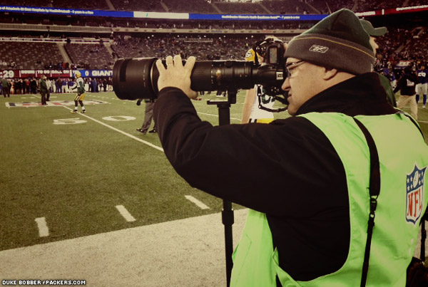 Long-time team photographer Jim Biever takes photos during pre-game warmups