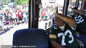 Former Packer Aaron Taylor waves to students