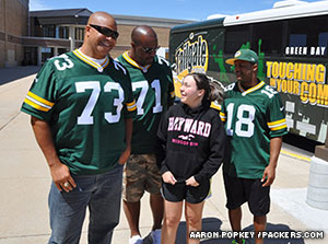Aaron Taylor, Santana Dotson, and Randall Cobb stand with a fan