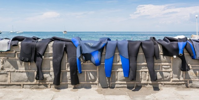 wetsuits drying on a wall overlooking the water