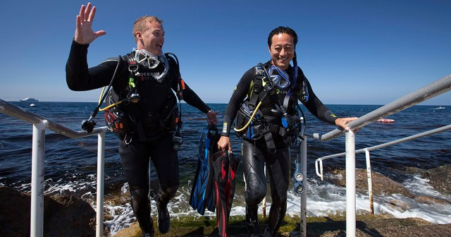 two scuba dive buddies exiting the water