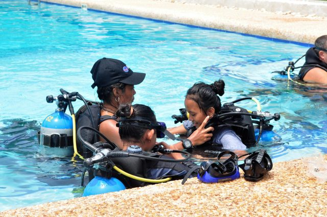 An instructor helps students with their gear