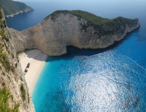 "Navagio Beach (Greek: Ναυάγιο), or Shipwreck Beach, is an exposed cove, sometimes referred to as ""Smugglers Cove"", on the coast of Zakynthos, in the Ionian Islands of Greece. It has been so named since 1983, when the alleged smuggler ship Panagiotis was wrecked on the beach while transporting cigarettes"