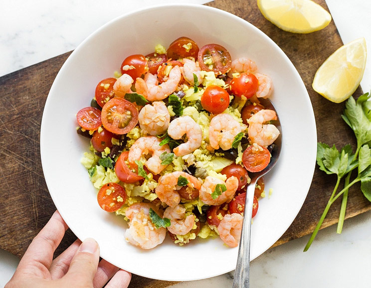 Season cauliflower couscous with fresh Mediterranean flavors like olives, capers, lemon, and parsley, and top with garlicky shrimp.