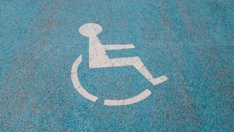 White Disabled Symbol Painted Onto Blue Surface