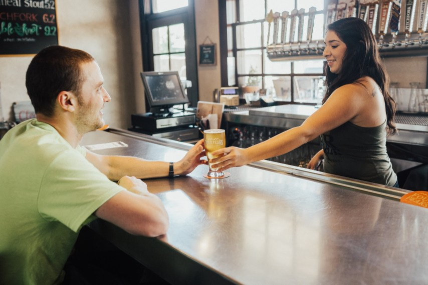 Woman handing glass of beer to man in green shirt