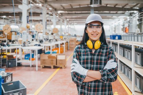 Portrait of young female industry manual worker standing in factory