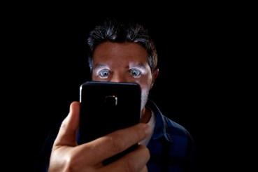 man kijkt op smartphone