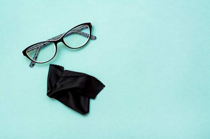 Bril met brillendoek en blauwe achtergrond