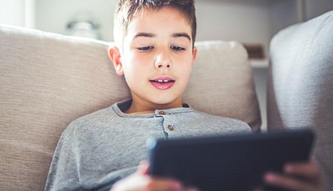 jonge kijkt op een smartphone op de bank