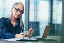 zakenvrouwmetleesbrilkijktinnotitieboekje
