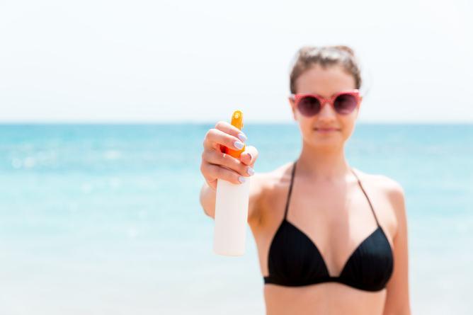 Vrouw beschermt ogen en huid tegen Uv-straling