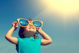 Kind kijkt met zonnebril naar de zon