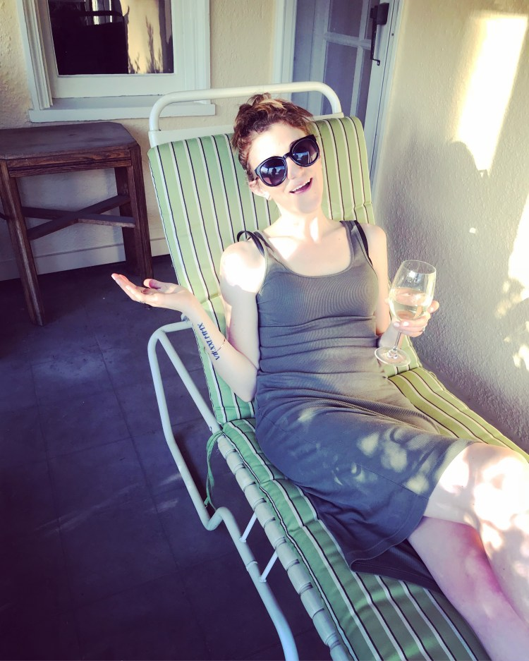 A woman wearing a pair of sunglasses, sitting on a patio chair, enjoying a glass of white wine in the sun.
