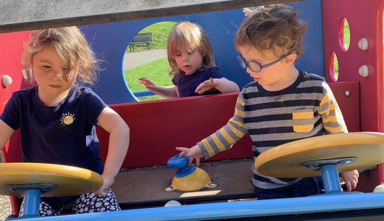 Three children playing outside at a playground.