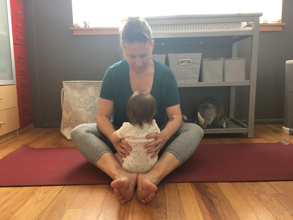 Megan facing baby on a yoga mat