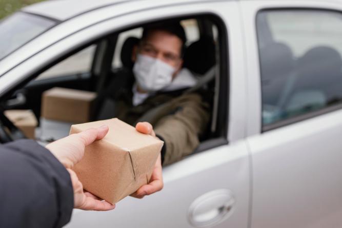 hombre entrega pedido desde auto