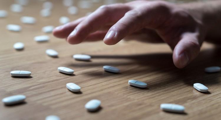 hand reaching for blue pills
